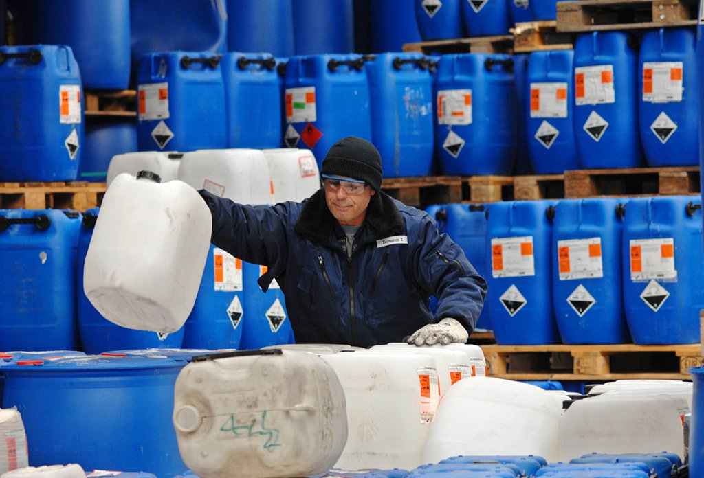 Ein Arbeiter sortiert leere Chemiefässer.